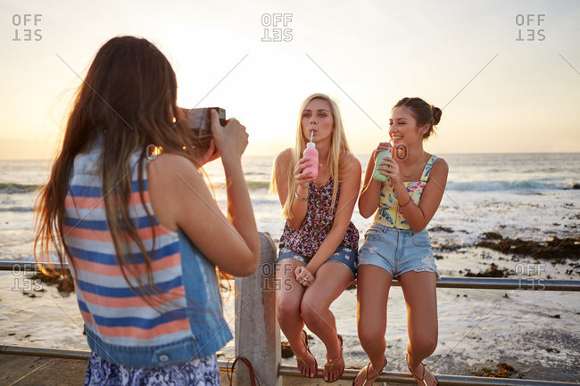 A young woman takes an instant photo of her friends at the beach