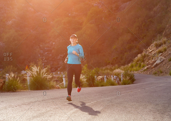 Woman running on a mountain road