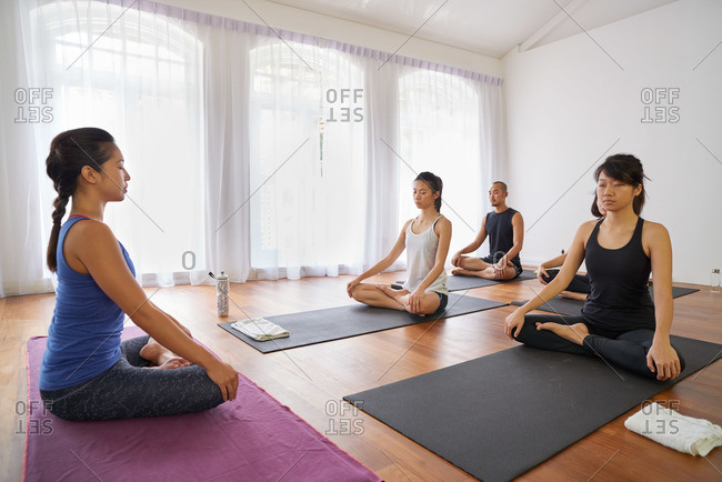 Instructor and students in a yoga class meditating