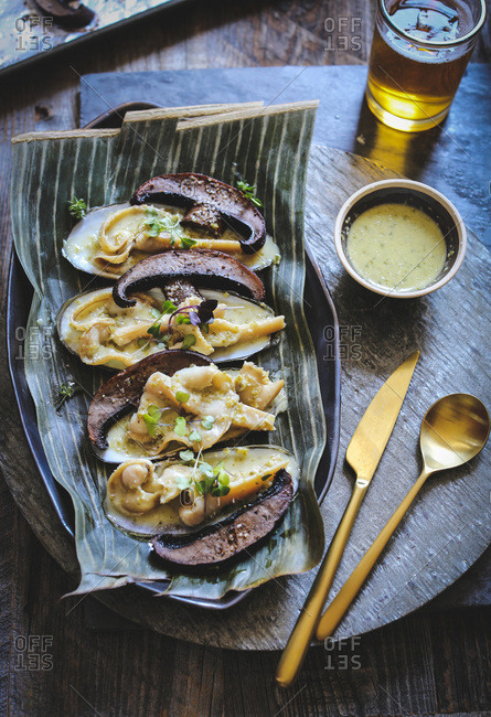 Razor clams with Portobello mushrooms and shishito pepper sauce served with a glass of beer