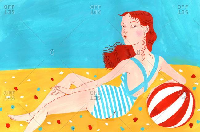 Redhead girl lying on the beach
