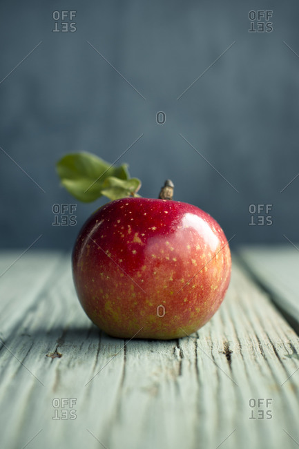 Single red apple on a rustic table
