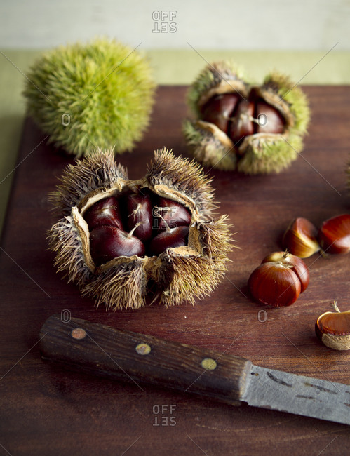 Chestnuts and a knife on a cutting board