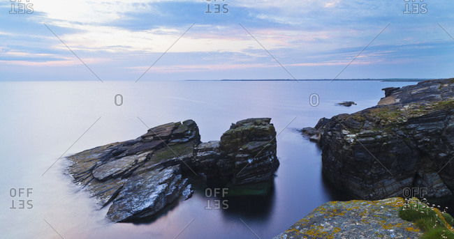Rocks and tranquil water along the coastline at dawn in Orkney, Scotland