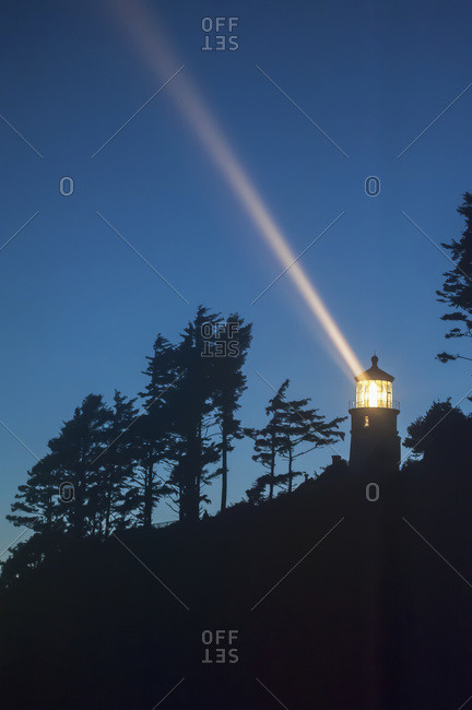 Heceta Head lighthouse shining through the oncoming darkness in Oregon