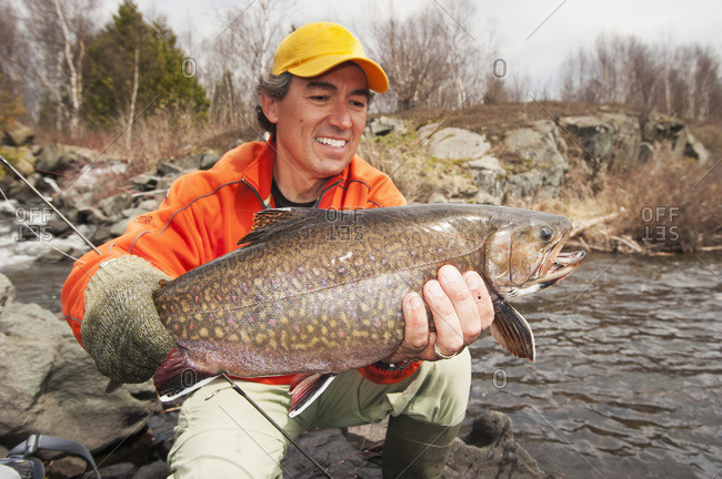 Angler holding a large brook trout (Salvelinus fontinalis) in Ontario, Canada
