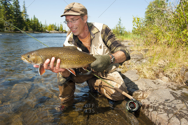 Angler with a large brook trout (Salvelinus fontinalis) in Ontario, Canada