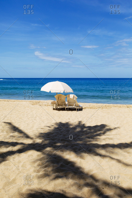 Beach chairs with umbrella on Hulupo\'e Beach, Manele Bay, Lanai, Hawaii