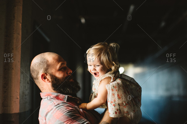 Dad holding laughing girl in hallway