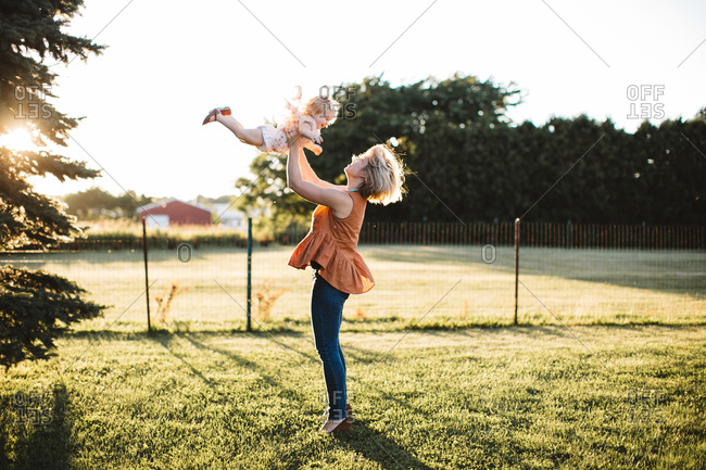 Mom playing with little girl in pastoral yard