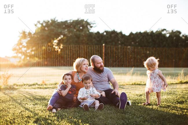 Family of five sitting in sun dappled yard