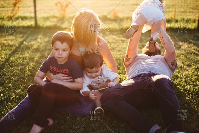 Family sitting in sun dappled rural yard