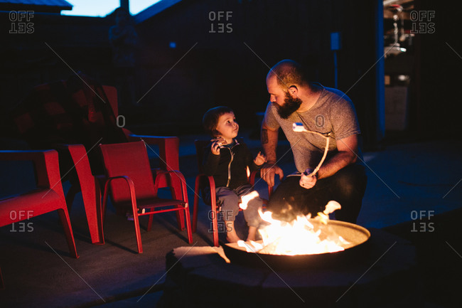 Dad and son making s'mores in backyard fire