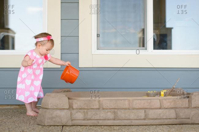 Girl dumping sand in sandbox