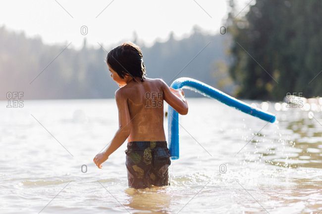 Boy holding a swim noodle in a lake