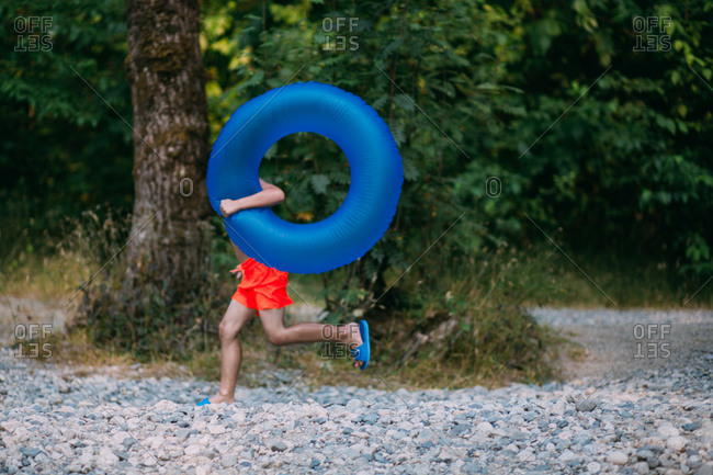 Boy running with an inflatable float