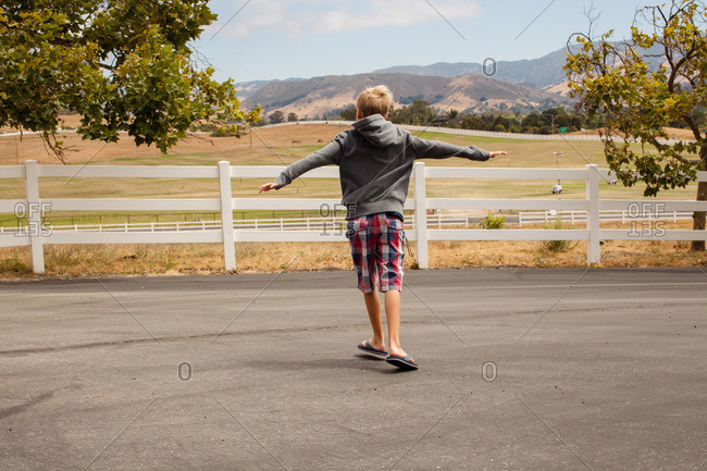 Boy walking with his arms spread overlooking mountains and pastures