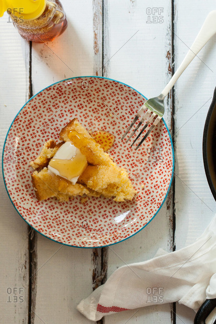 Cornbread on a plate with butter and honey
