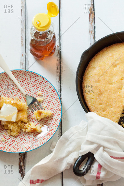 Cast iron skillet and slice of fresh cornbread on a plate