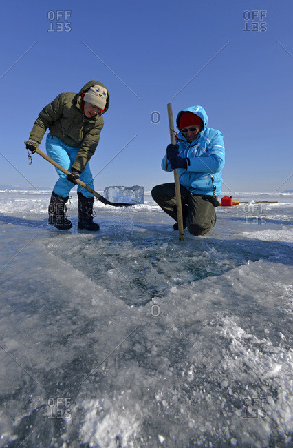 Two people prepare an ice hole for ice diving