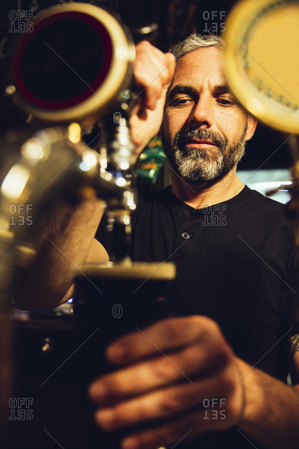 Portrait of a man pouring beer in an Irish pub