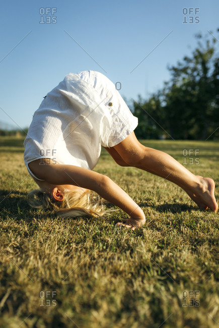 Little girl doing a somersault on a meadow