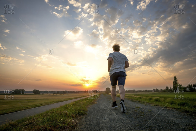 Rear view of man jogging at sunset