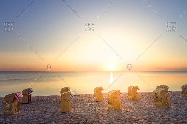 View to Timmendorfer Strand with hooded beach chairs at sunrise, Niendorf