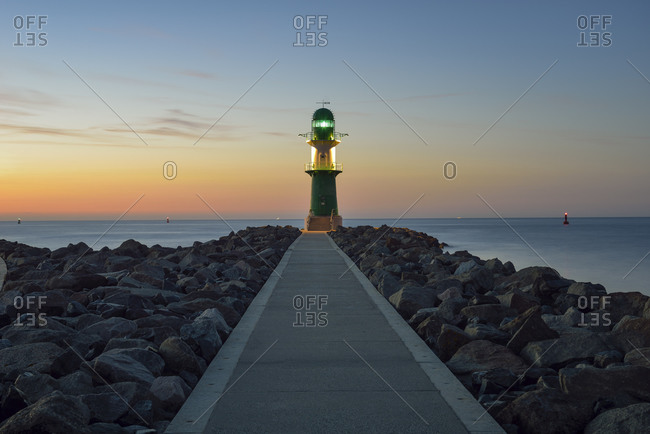 View to lighthouse at dusk in front of the Baltic Sea, Warnemuende