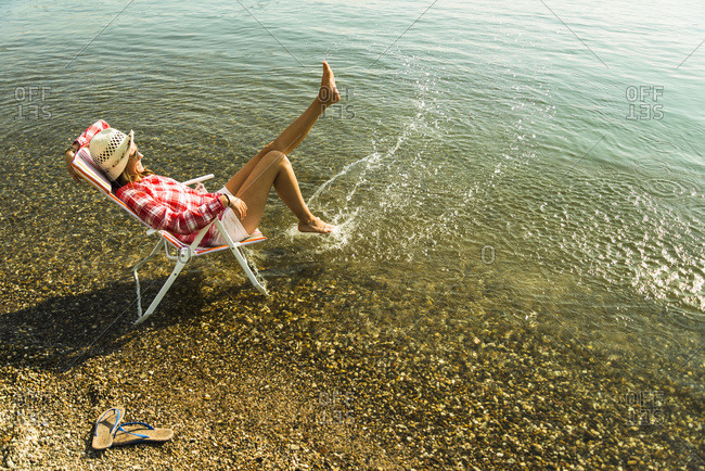 Young woman sitting on deckchair in river splashing with water
