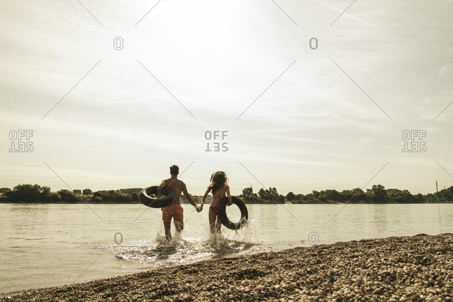 Young couple running with inner tubes in river