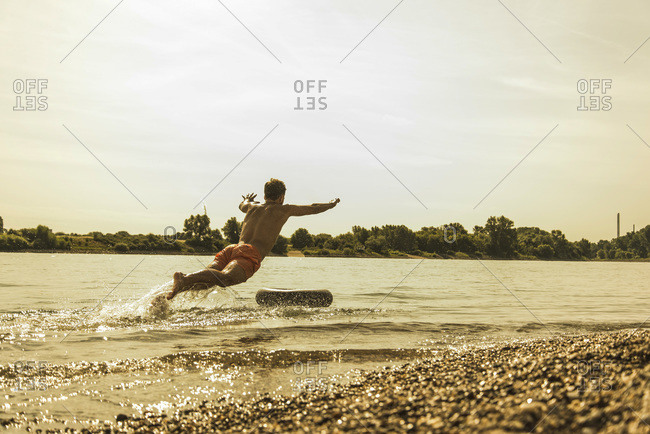 Young man jumping in river with inner tube