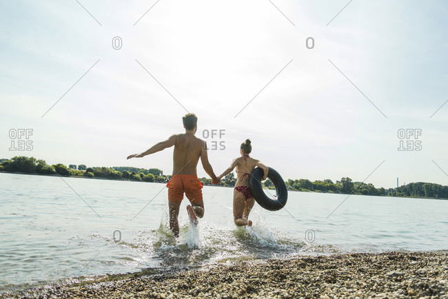 Young couple running with inner tube in river
