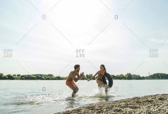 Playful young couple with inner tube in river