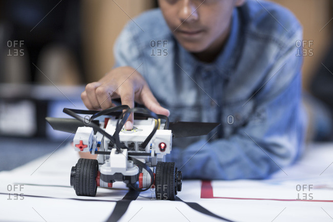 Schoolboy in robotics class testing vehicle on test track
