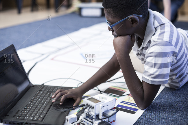 Schoolboy with laptop in robotics class testing vehicle on test track