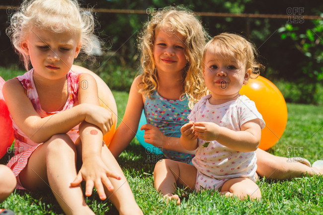 Three young girls sitting on grass with bright colored balls
