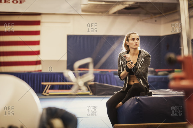 A gymnast takes a break during practice