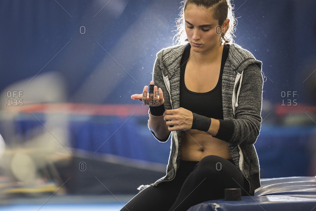 A gymnast wraps her hands before practice