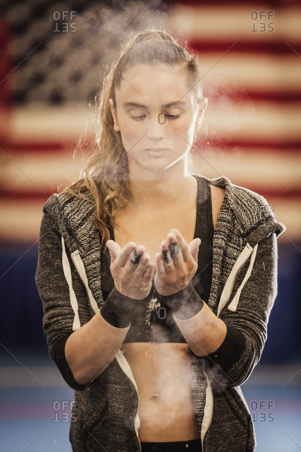 A gymnast powders her hands in front of the U.S. flag