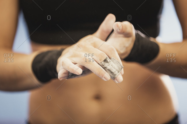 Close-up of a gymnast's chalk-covered hands