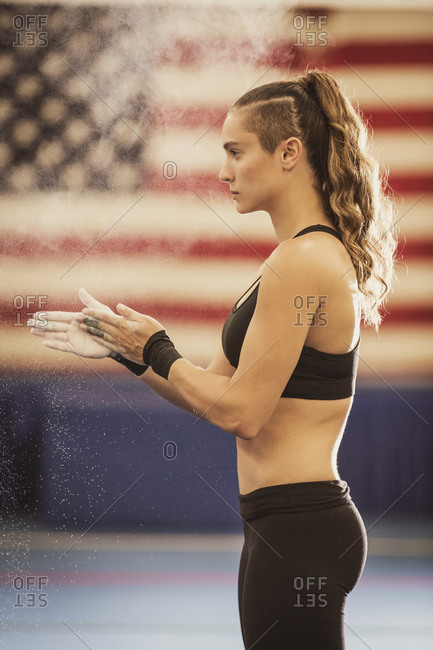 An American gymnast chalks her hands during training
