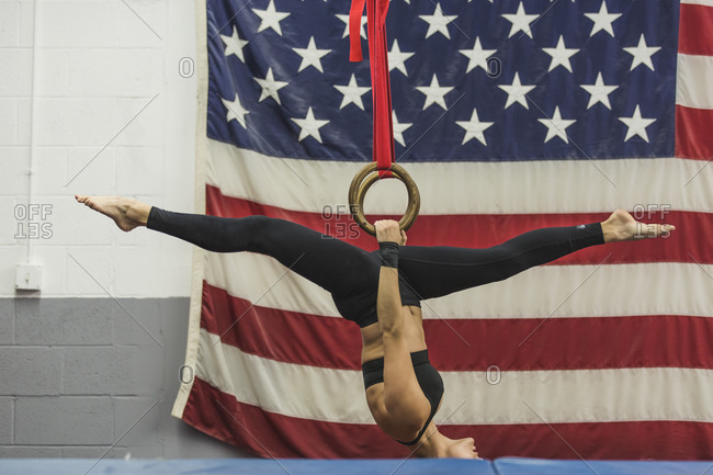 A gymnast does an upside-down split on the rings