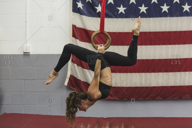 A gymnast practices on the rings