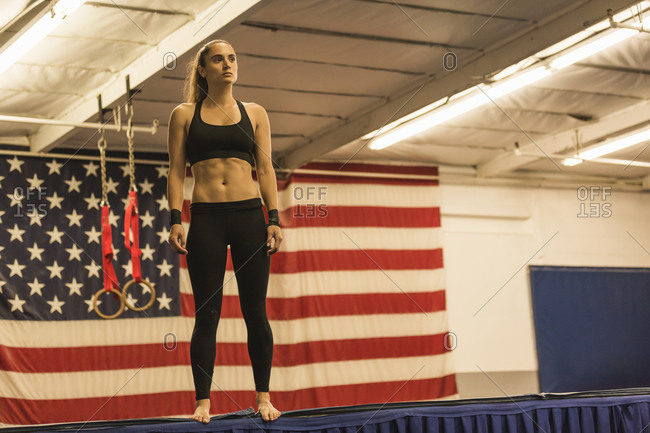 A gymnast stands on the edge of a platform