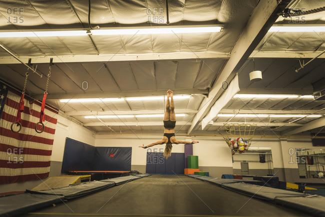 A gymnast flips upside-down