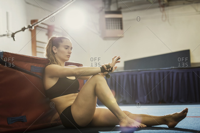 A gymnast leans against a mat