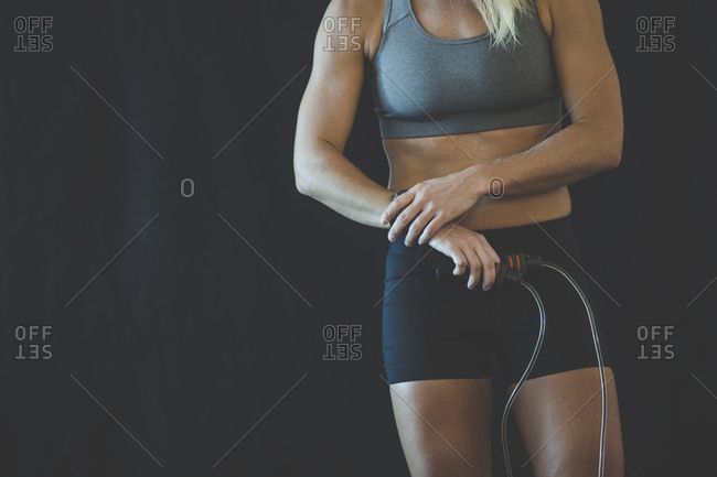 Woman exercising with jump rope checking her watch