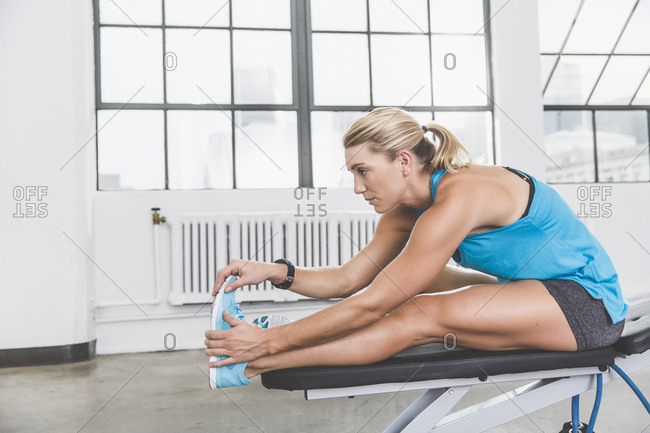 Woman doing leg stretches in a gym