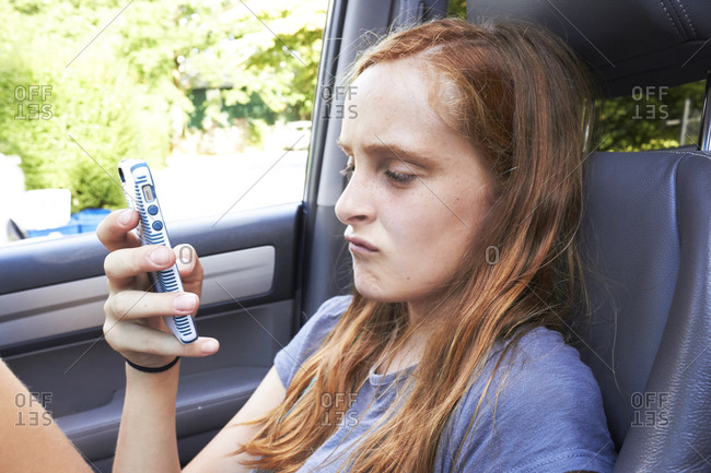 Girl checking her phone while sitting in a car
